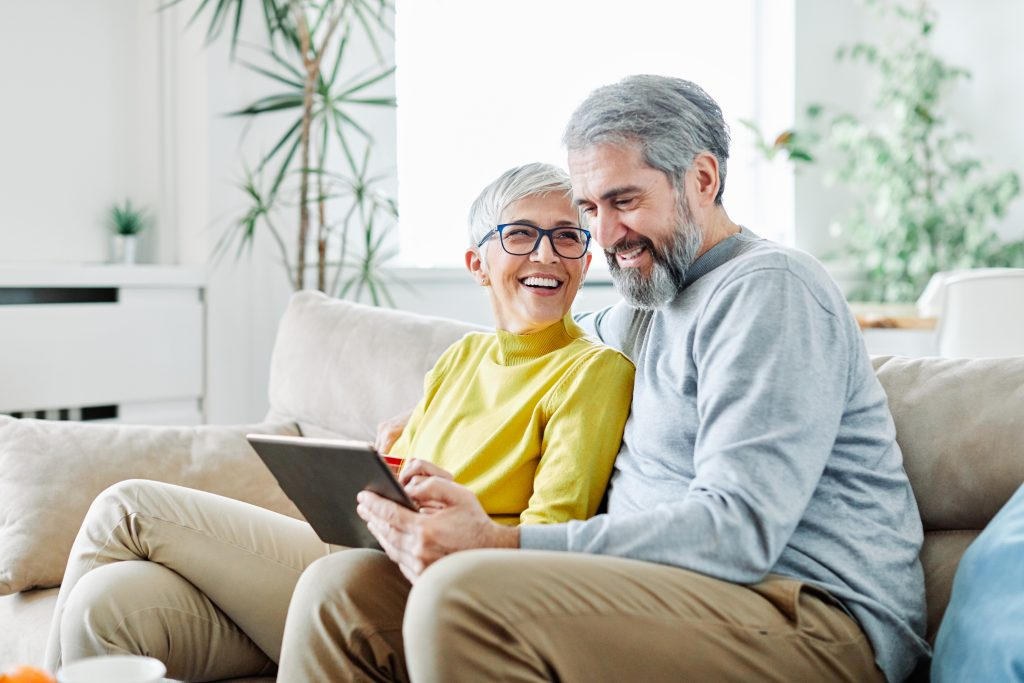 portrait of happy smiling senior couple using tablet at home